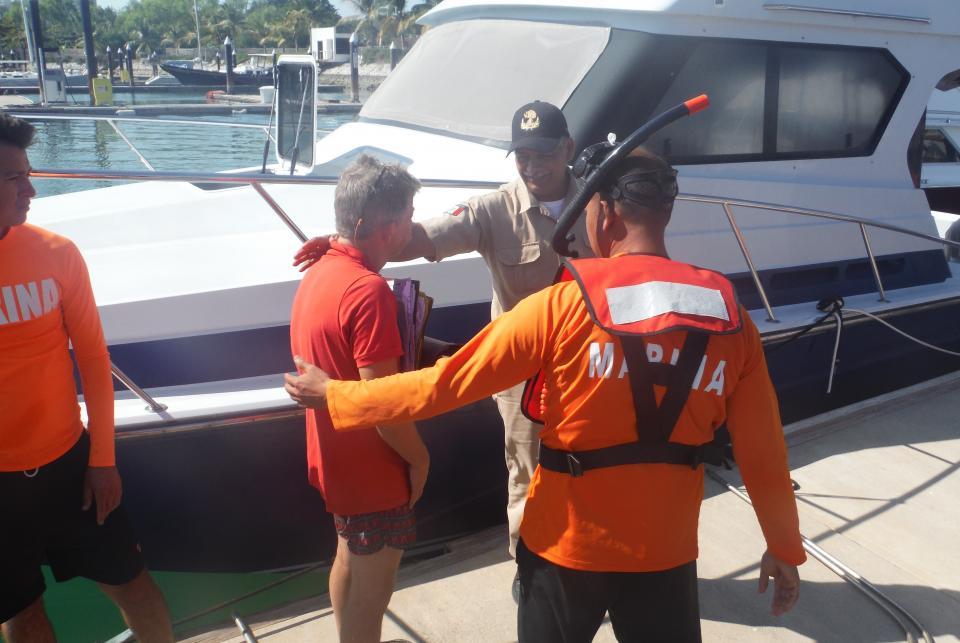 Marinos auxilian a una persona a  bordo de un velero que encalló