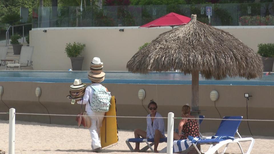 Hombre vendiendo sombreros en la playa