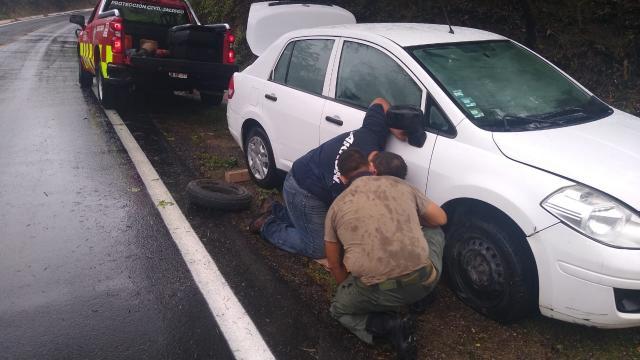 Dos personas cambiando la llanta de un vehículo