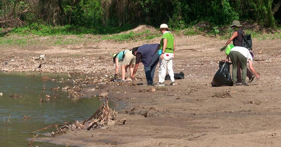 Personas juntando basura en la orilla de un río