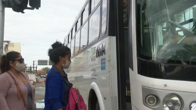 Dos mujeres con cubrebocas abordando transporte público