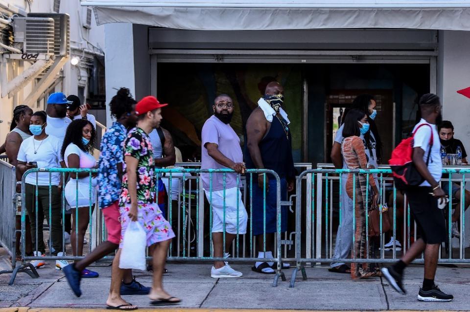 Personas esperan turno para entrar a un restaurante en Miami