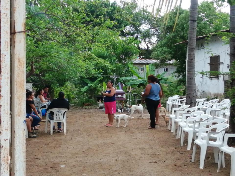 Personas en un velorio en el patio de una casa