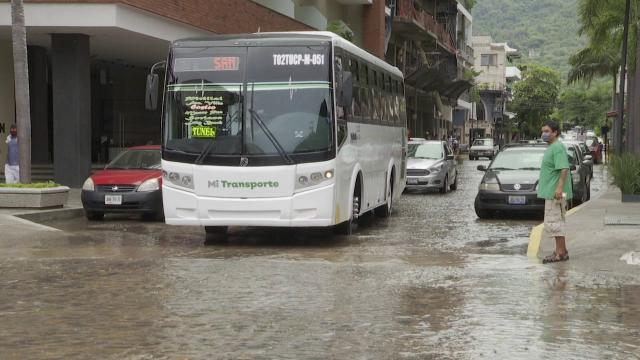 Transporte público pasando por una calle inundada