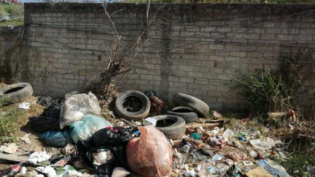 Terreno baldío lleno de basura y escombro