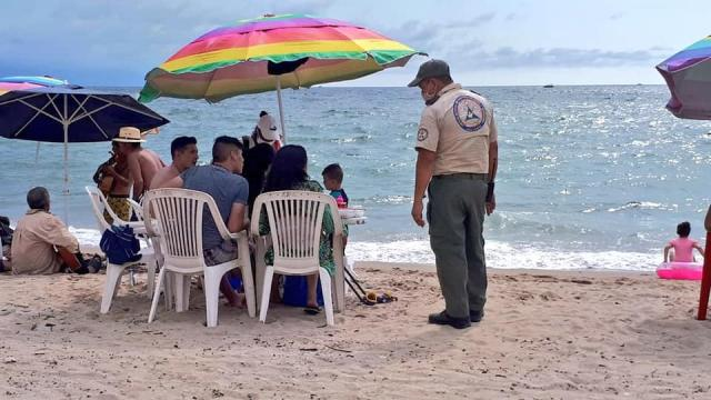 Elemento de protección civil dando indicaciones a turistas