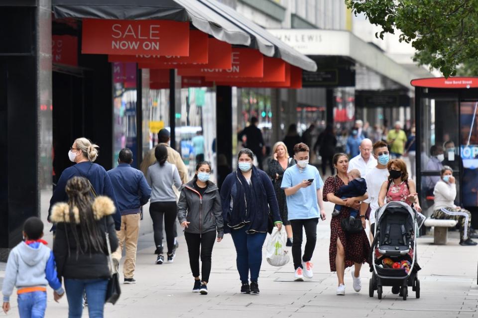 gente con cubrebocas caminando por una calle