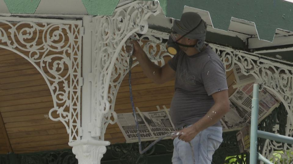 Personal de mantenimiento pintando un kiosko