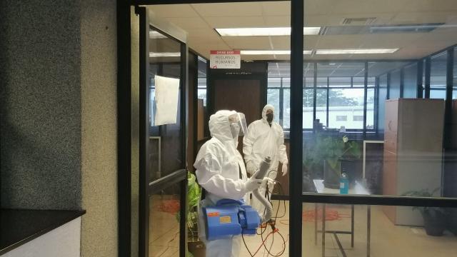 Equipo de sanitización, desinfectando una oficina