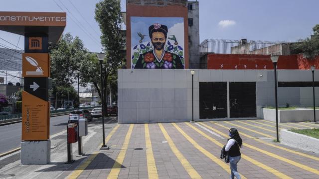 mujer caminando, al fondo se ve un mural de Frida Kahlo