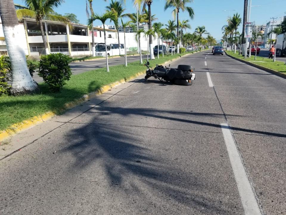 Motocicleta volcada en avenida