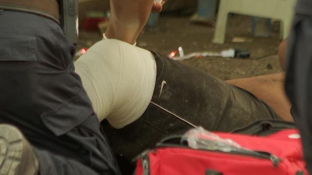 Paramédicos atienden a un indigente que cayó de un segundo piso