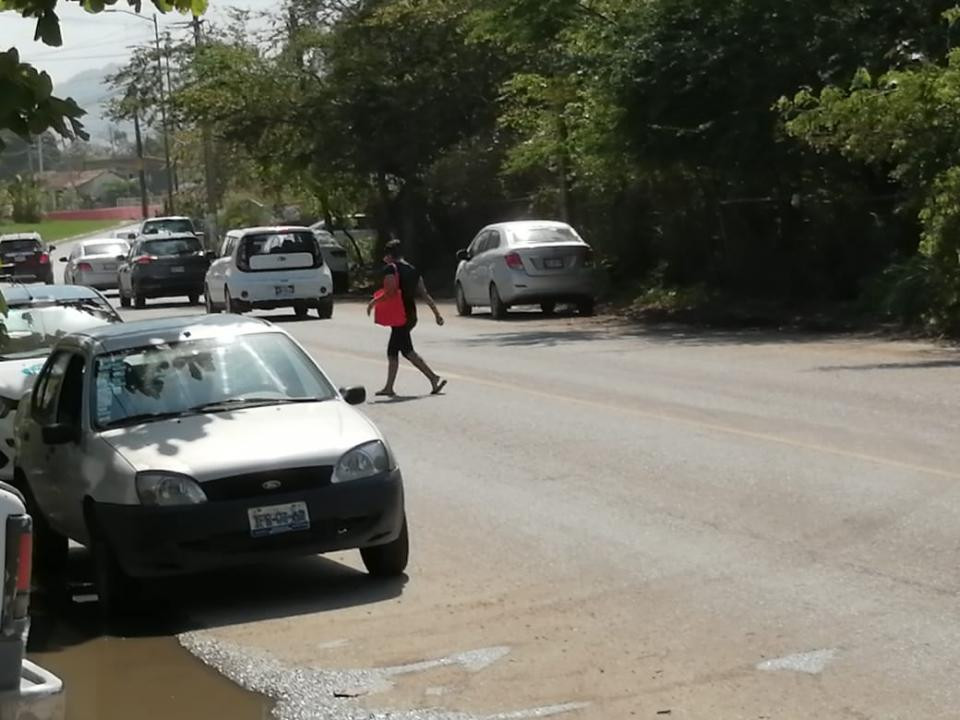 Mujer cruzando una avenida transitada