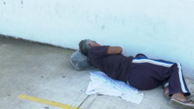 Persona de la tercera edad esperando a fuera de una clínica del IMSS