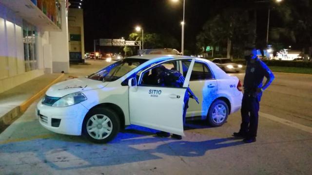 Elementos de seguridad inspeccionando un taxi