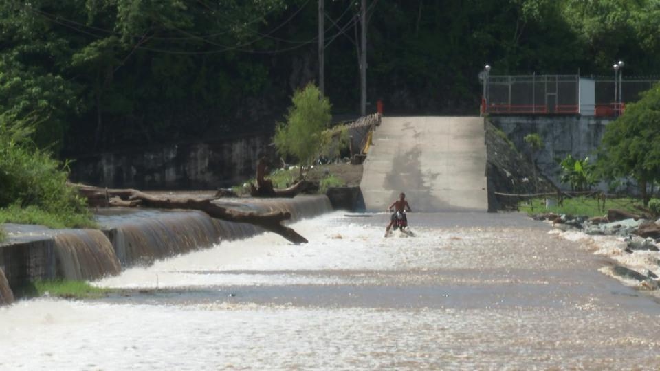 motociclista pasando por una calle inundada