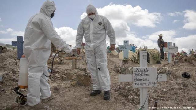 Personas con equipo de protección sanitaria en Panteón