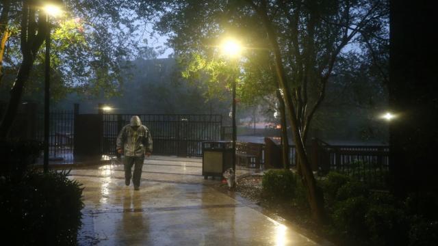 Un hombre camina hacia su hotel durante el huracán Delta