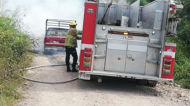 Bomberos apagando incendio en una camioneta