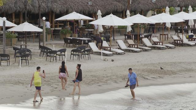 Turistas caminando en playa en Puerto Vallarta