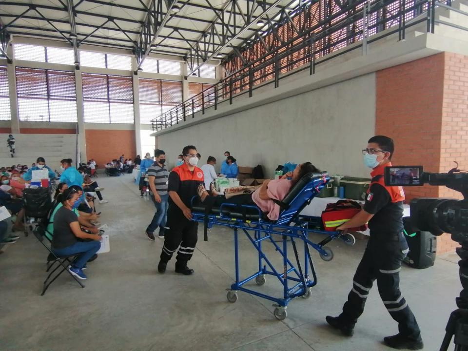 Paramédicos auxiliando a mujer tras recibir vacuna contra Covid-19