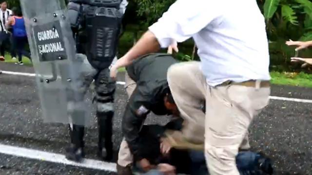 Agente mexicano pisando cabeza de migrante